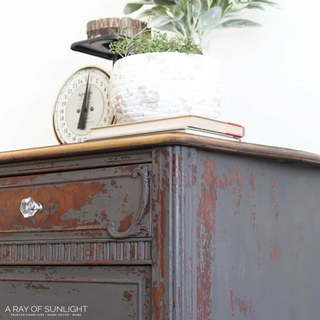 How to Use Powdered Milk Paint on your thrifted, old bedroom dresser to create an old worn farmhouse style look. The warm gray milk paint chipped and left the old wood finish showing underneath in some places. The top and legs were sanded down to bare wood and sealed with Hemp Oil.