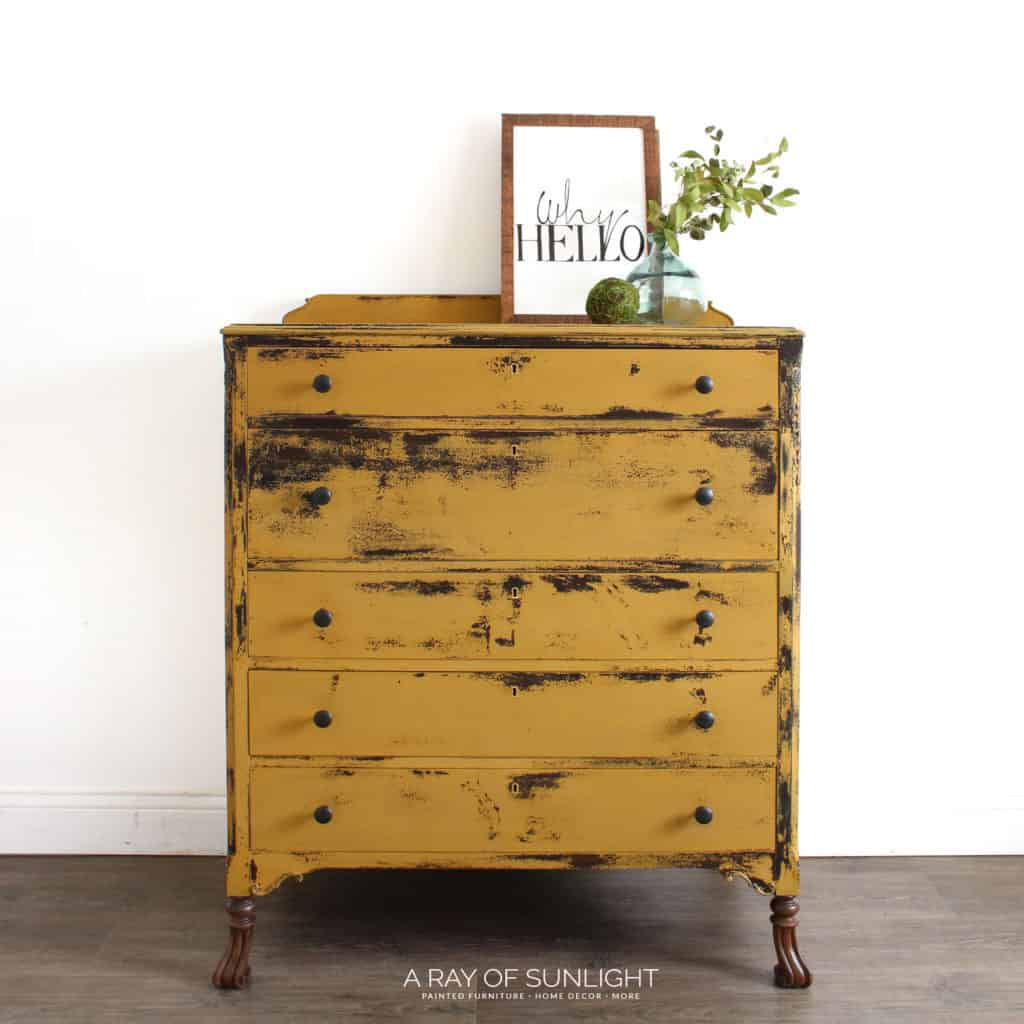 Full view of mustard yellow chippy dresser with wood feet