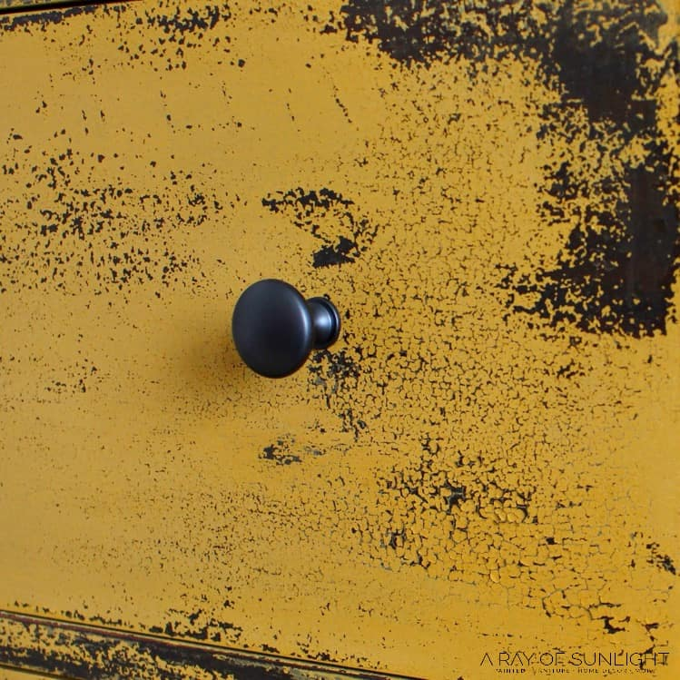 Closeup of chippy yellow paint and black knob