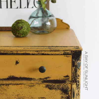 How to Paint a DIY Chippy Painted Dresser. A super easy way to makeover your thrift finds for a farmhouse style, old distressed style. This mustard yellow bedroom DIY uses natural milk paint powder and very little sanding. By A Ray of Sunlight