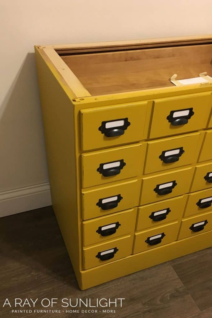 card catalog hardware on mustard yellow dresser