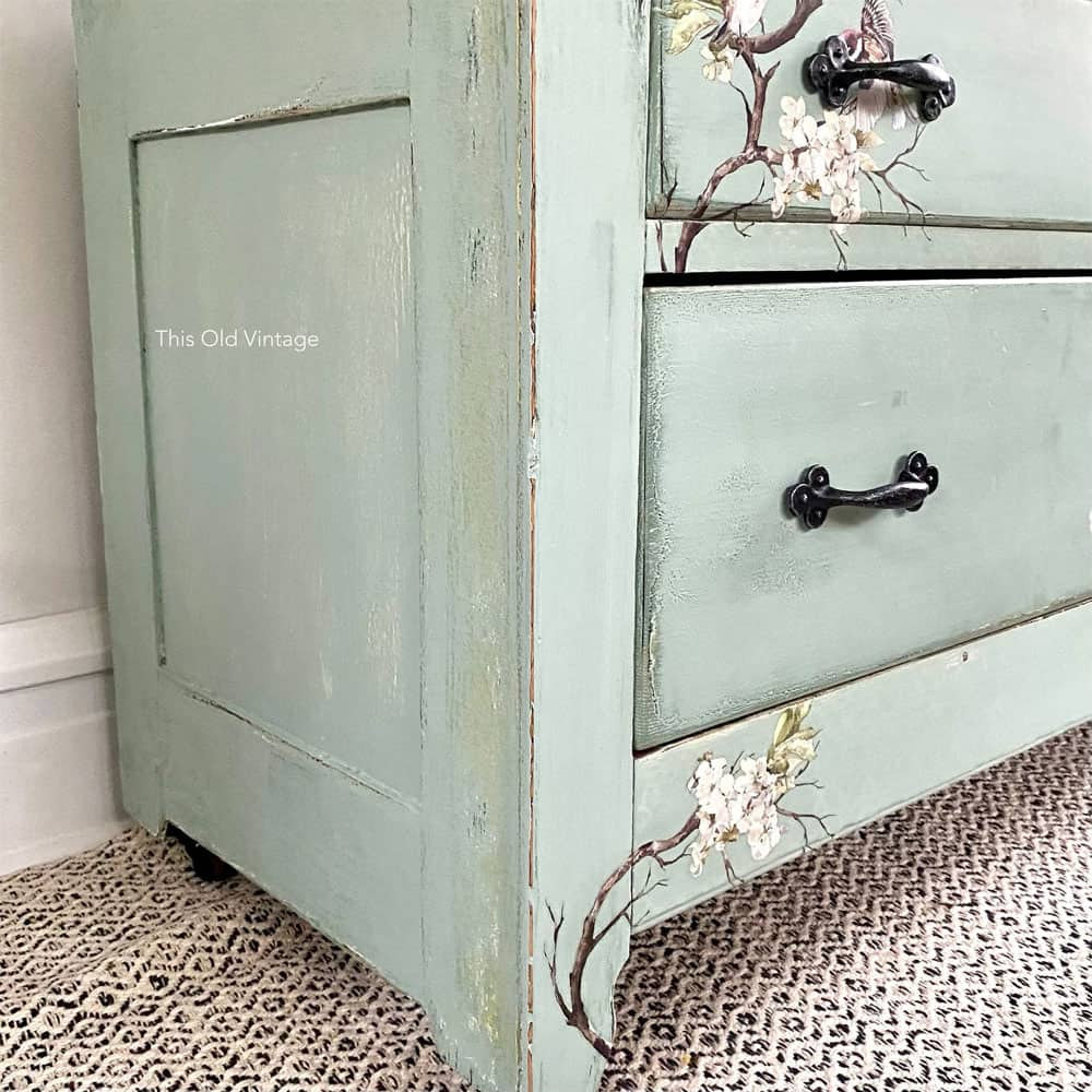 Closeup of blue distressed dresser with yellow and green paint underneath