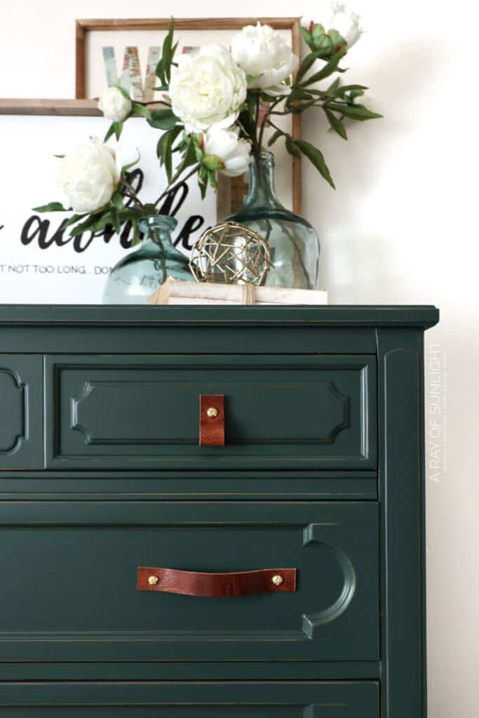 tight shot of green chalk painted dresser with leather drawer pulls.