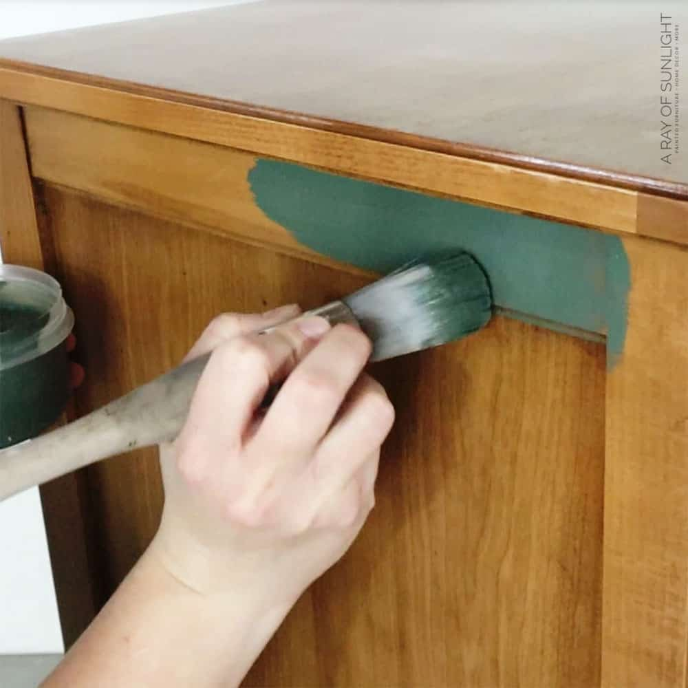 brushing first coat of green chalk paint on with round paint brush.