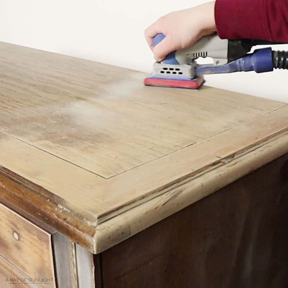 sanding the top of the cedar chest with a power sander