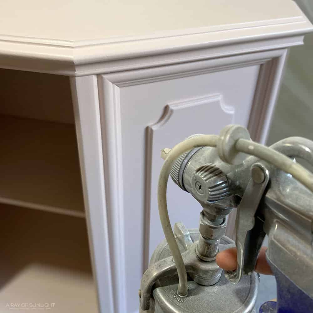 spraying light pink paint on cabinet with paint sprayer