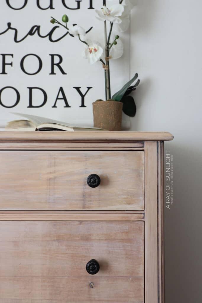 closeup of DIY whitewash dresser makeover with dark knobs