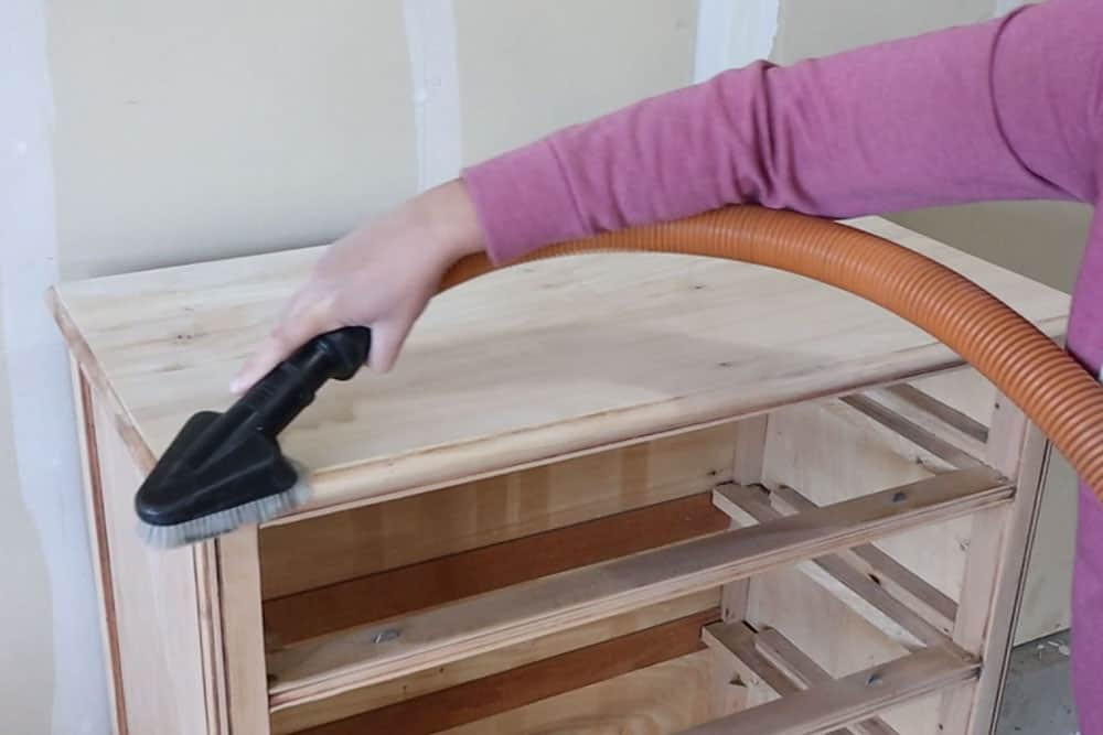 using a hose shop vacuum attachment to remove dust from the dresser