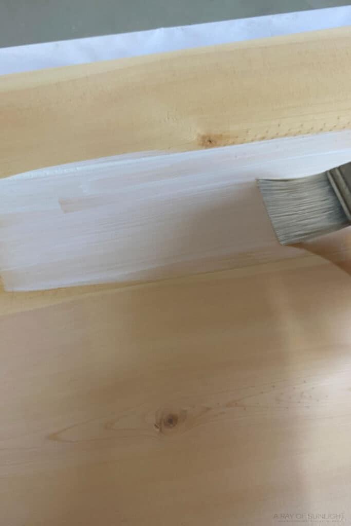 brushing whitewash on pine wood