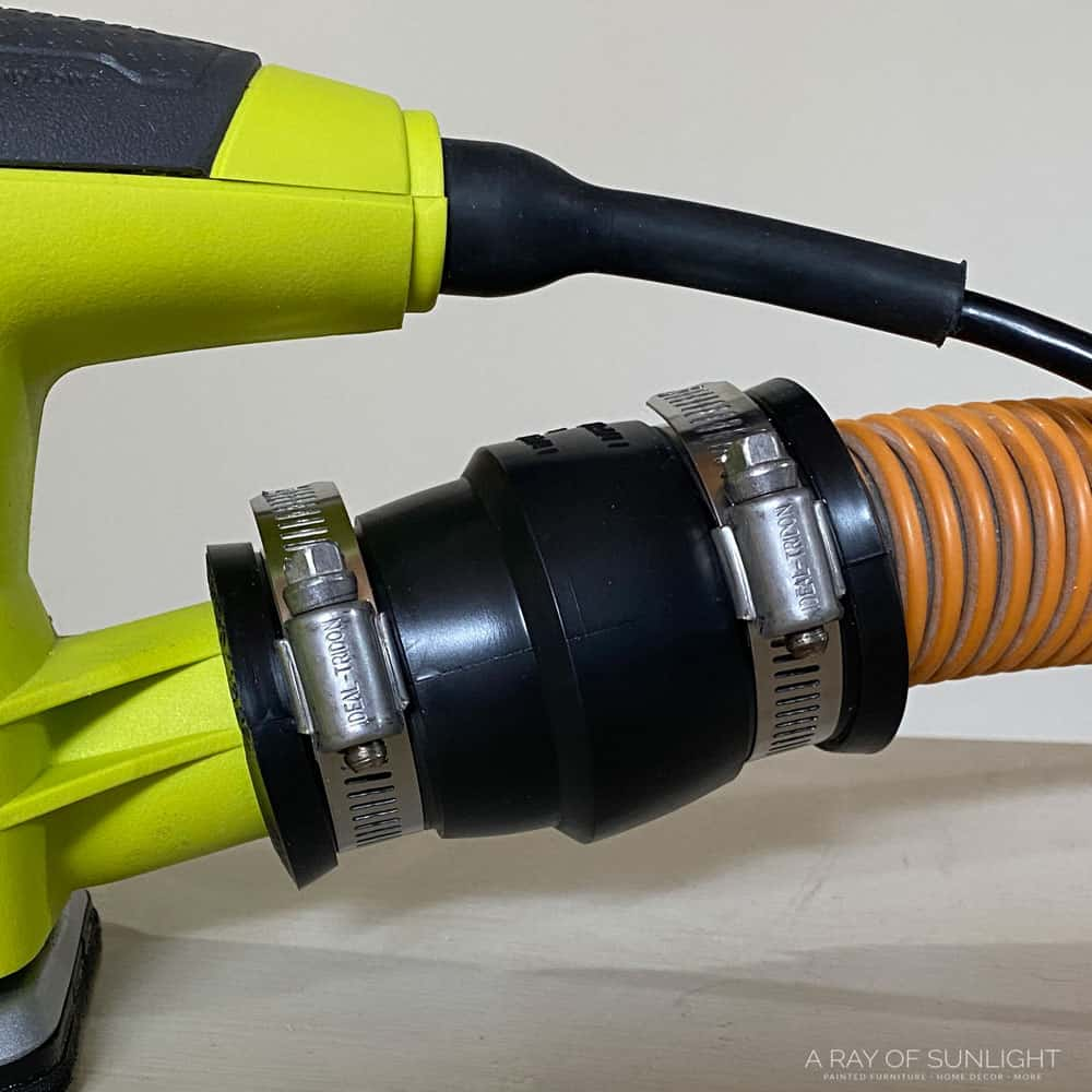 closeup of ryobi detail sander attached to shop vac hose with adapter
