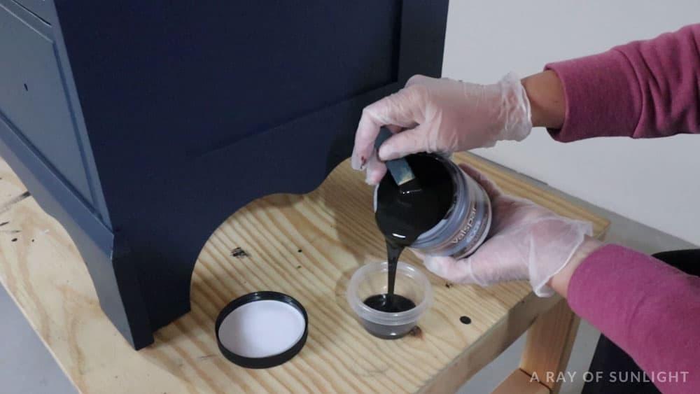 Pouring valspar antiquing glaze into a bowl