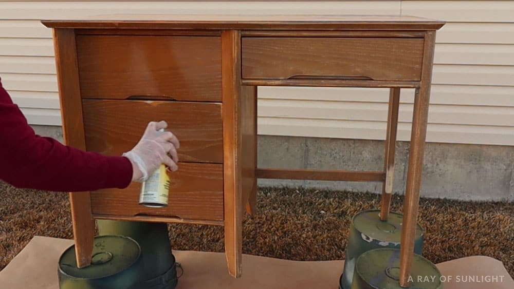 spraying clear shellac onto the desk outside