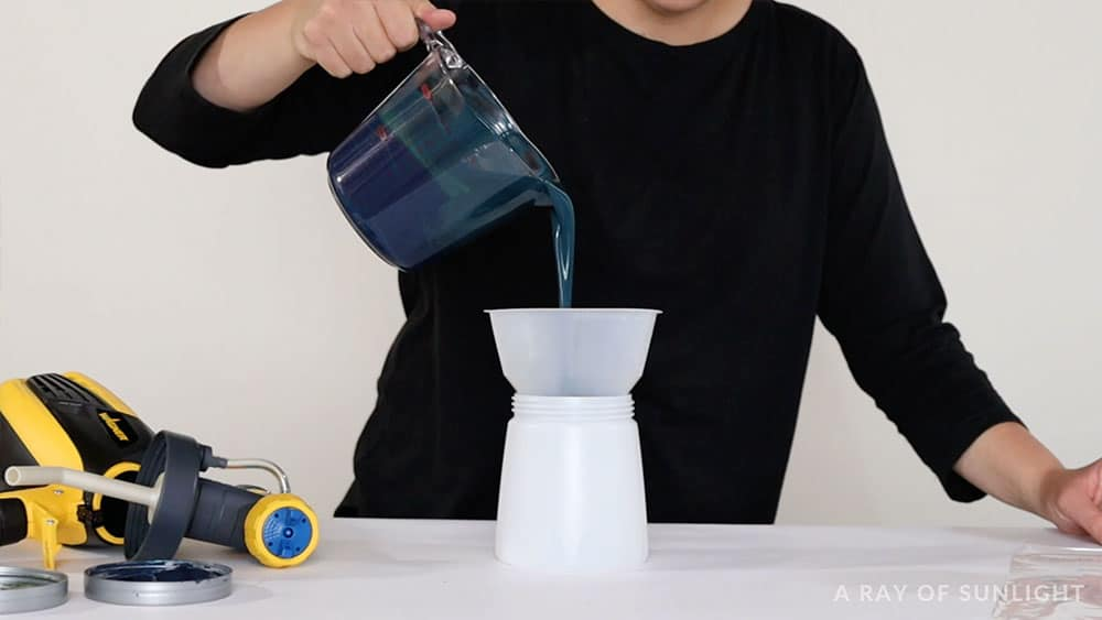 pouring chalk paint into a filter into the paint sprayer container