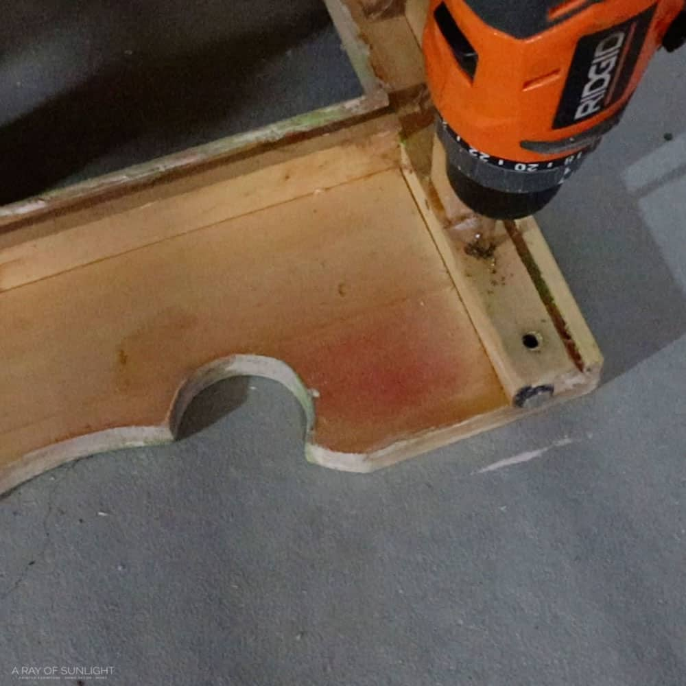 Using a drill to unscrew and detach the base detail.