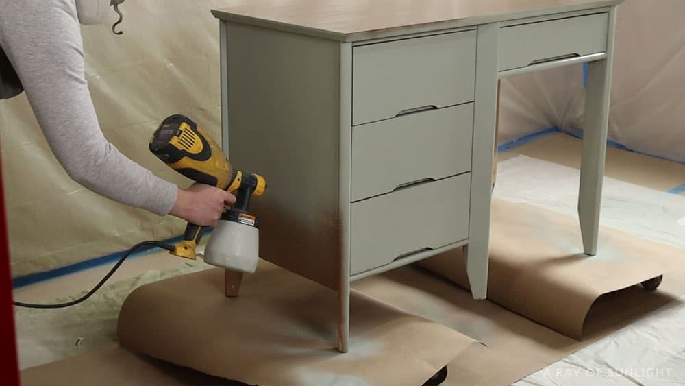 spraying chalk paint onto the desk with a wagner paint sprayer