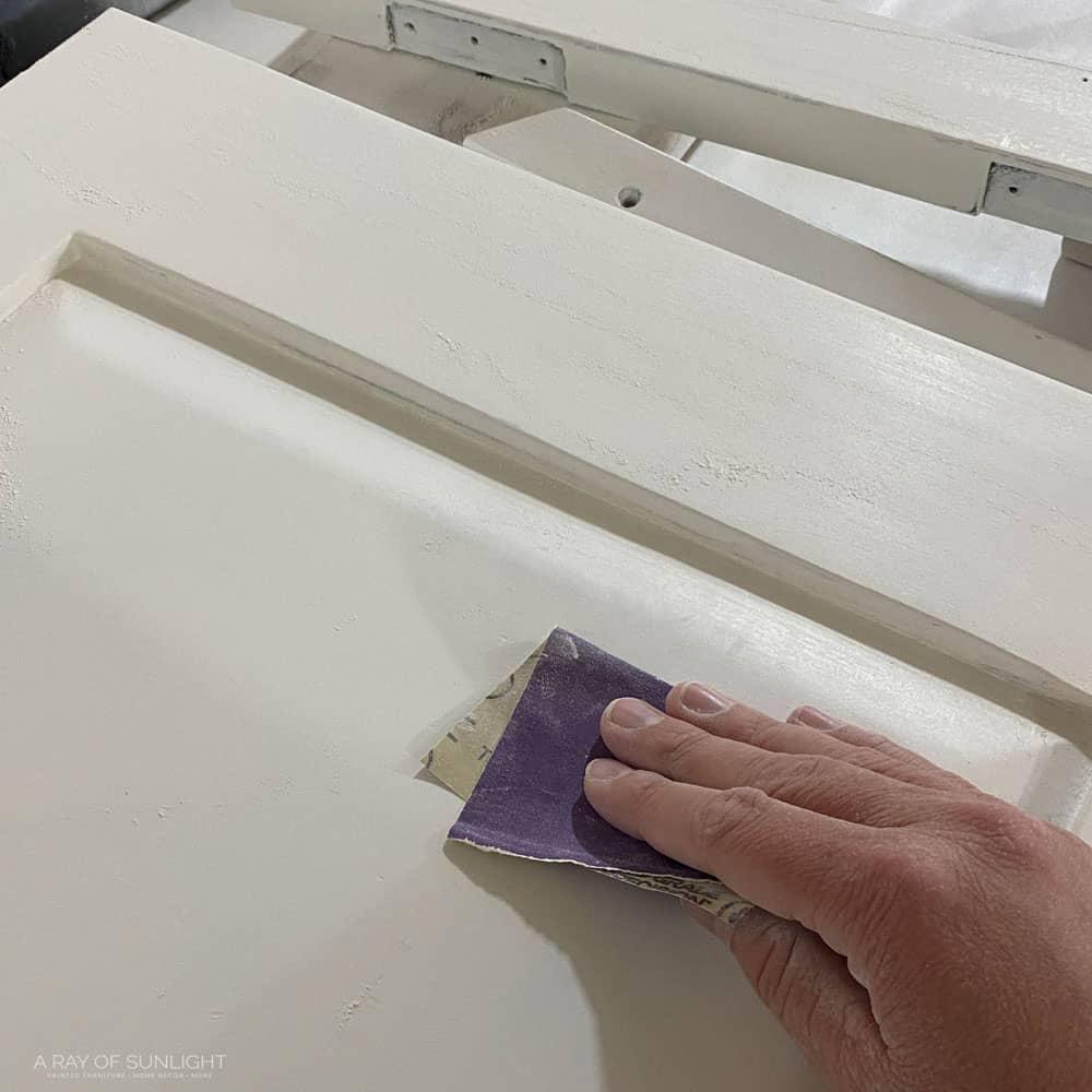 Sanding white paint between coats.