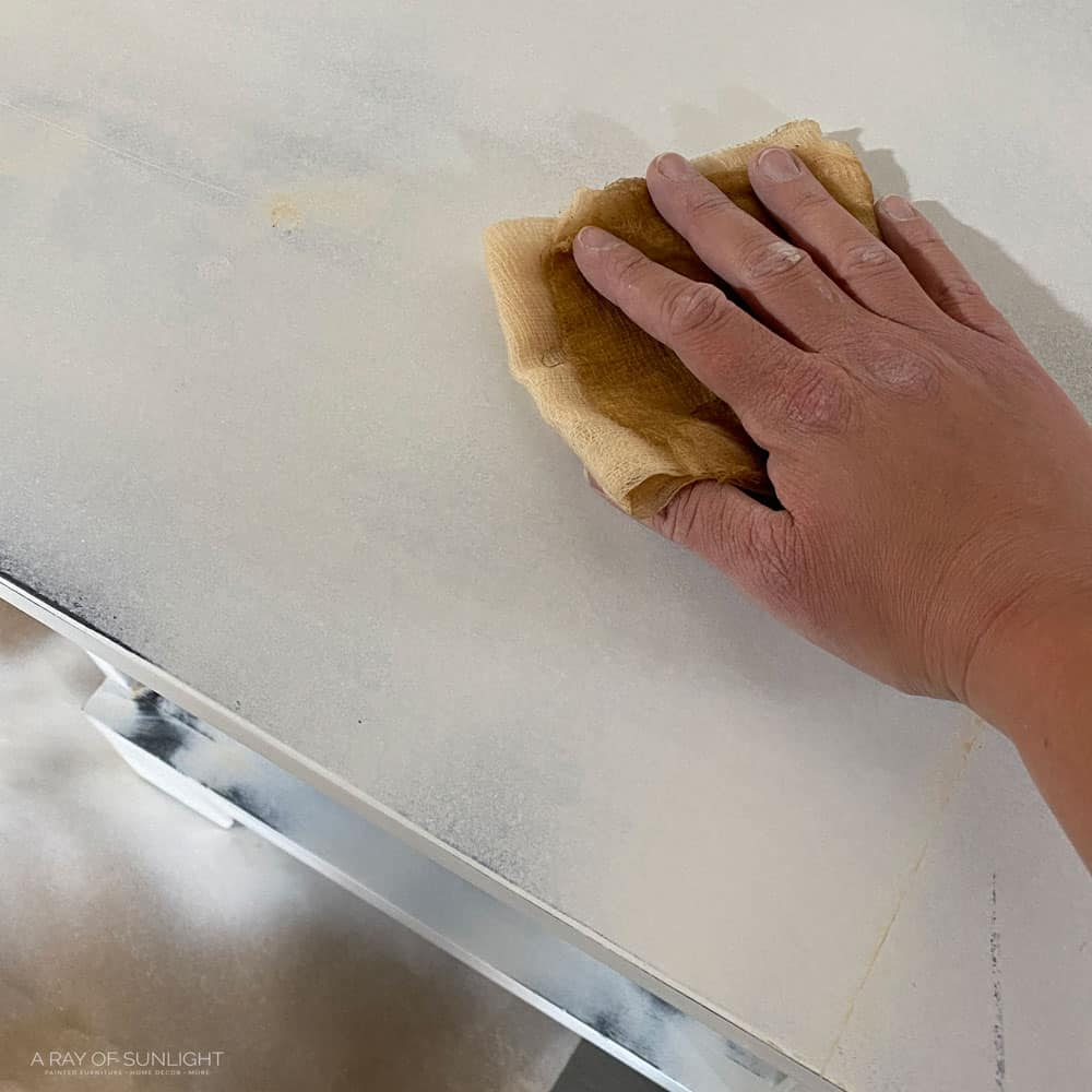 Wiping off dust with a tack cloth.
