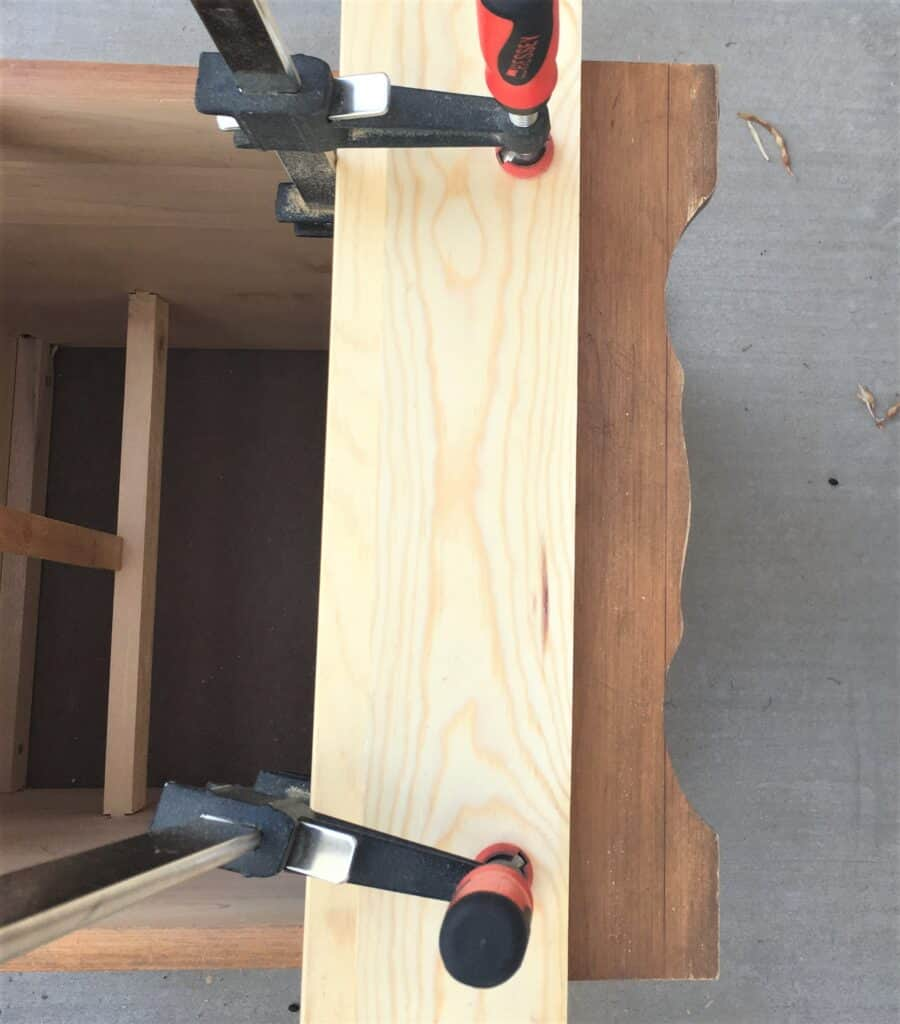 wood clamped to the bottom of the nightstand for a straight edge