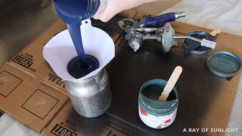 pouring chalk paint into a filter on the paint sprayer container