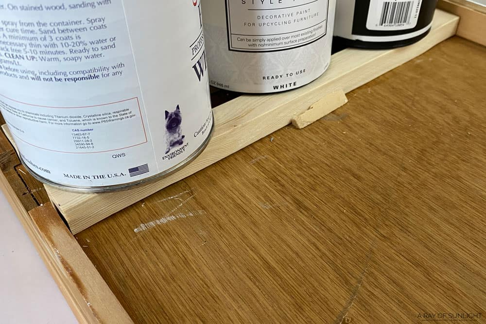 paint cans on holding drawer tracks in place while the glue dries
