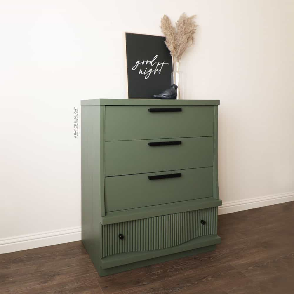 side shot of green painted diy fluted dresser with black hardware
