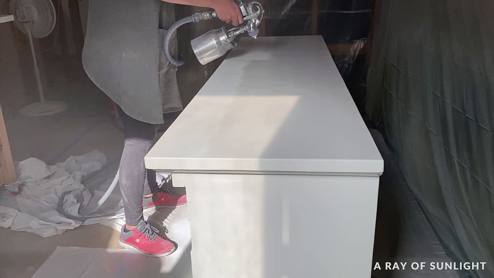 spraying the top of a white tv stand