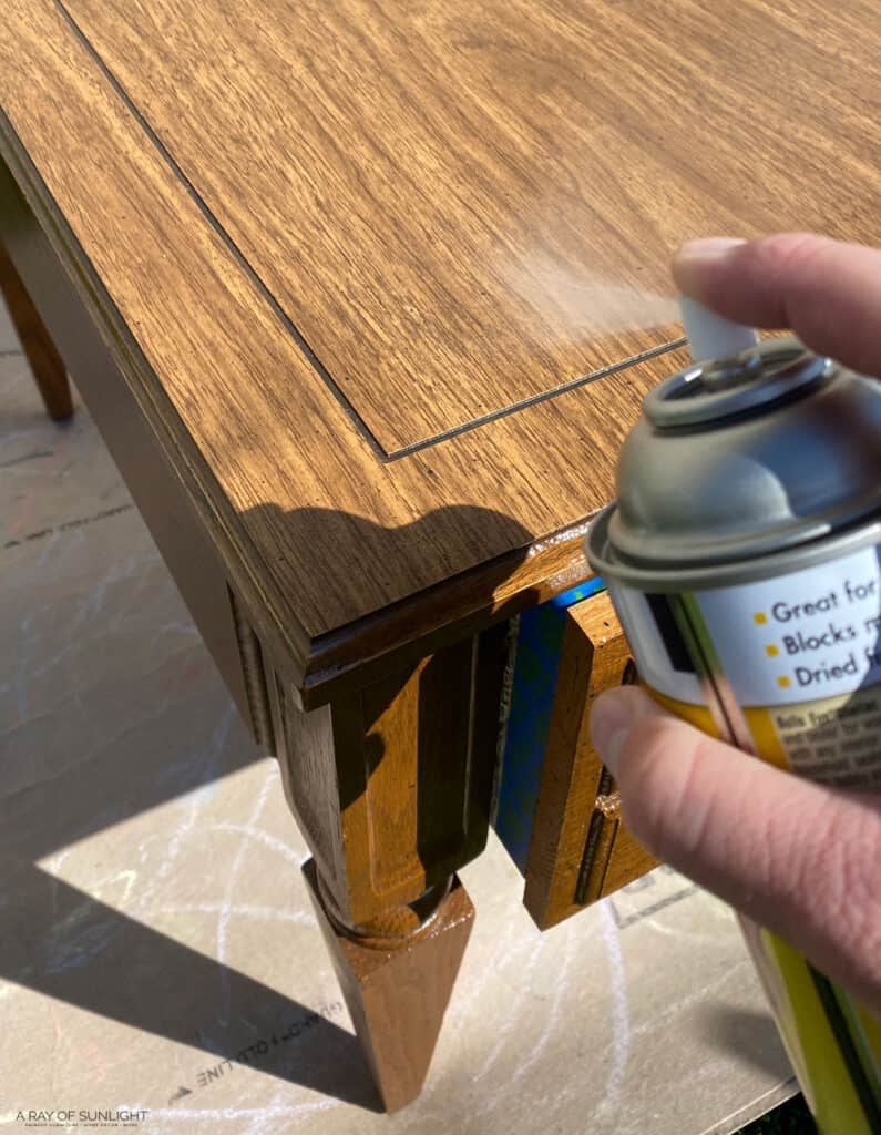 spraying clear shellac on the end table