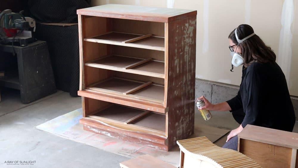 spraying clear shellac on dresser