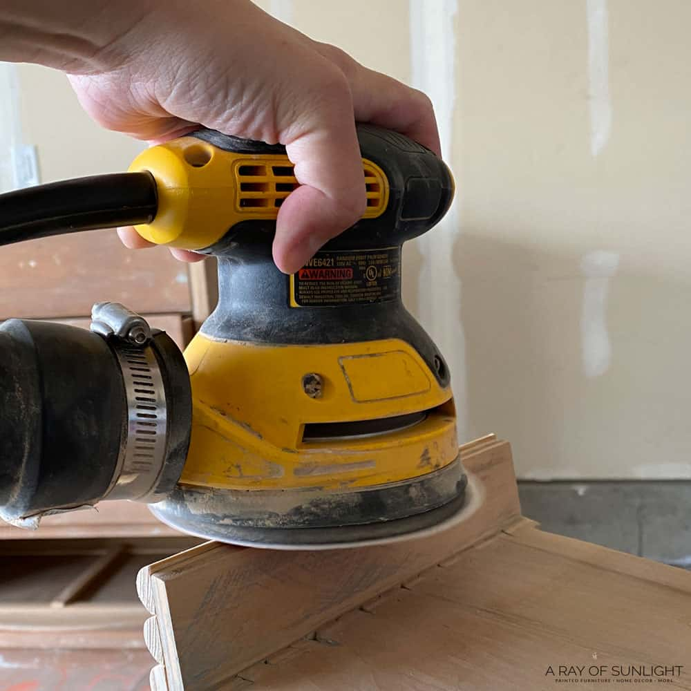 sanding side of drawer down with orbital sander where the dowel went over the edge