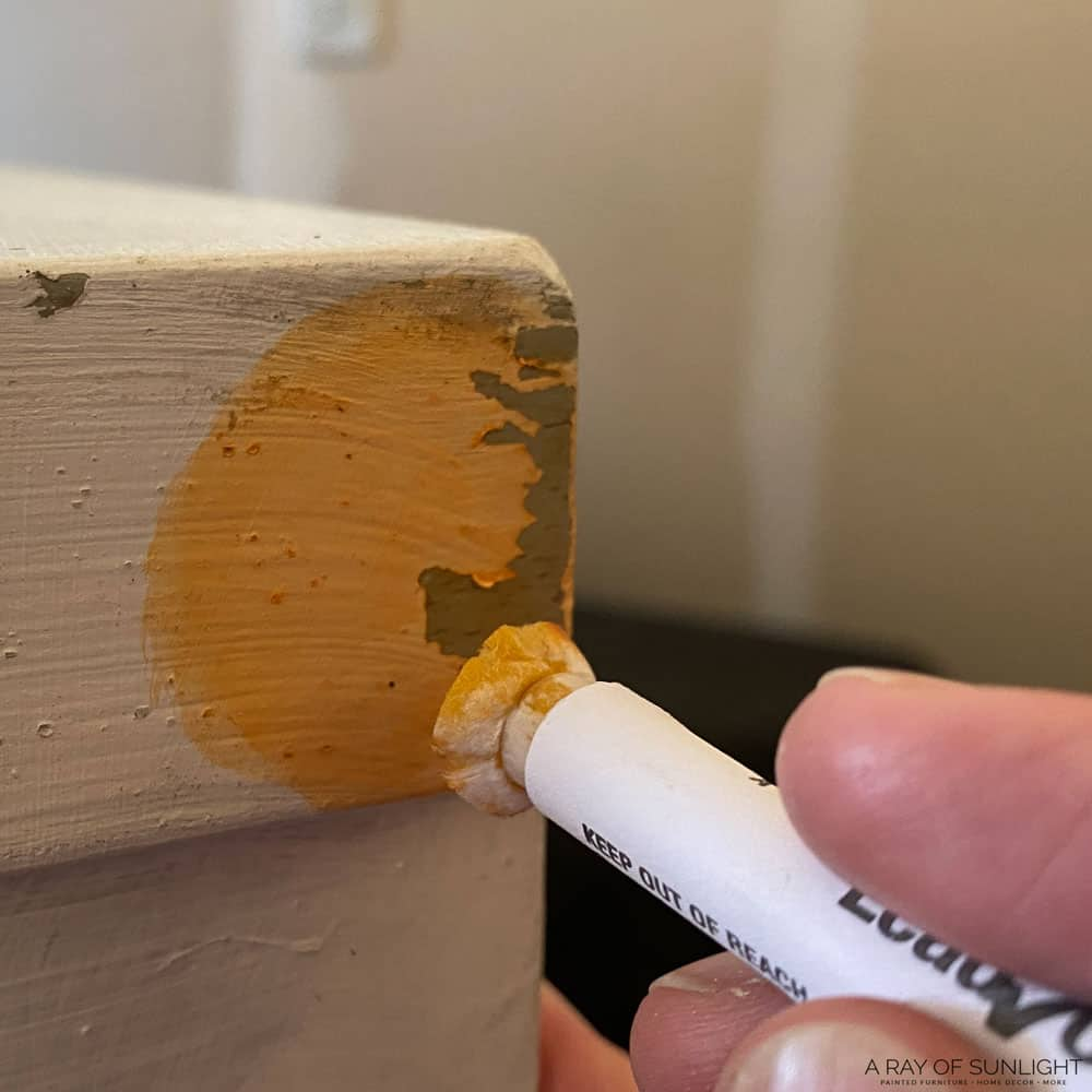 rubbing the lead test onto a painted wood dresser