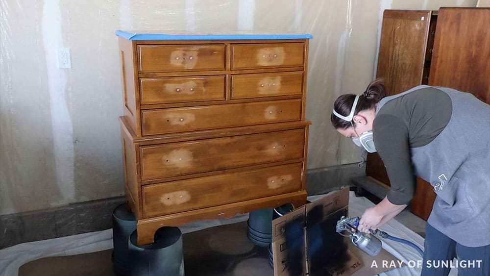 spraying paint onto a cardboard box before spraying the dresser